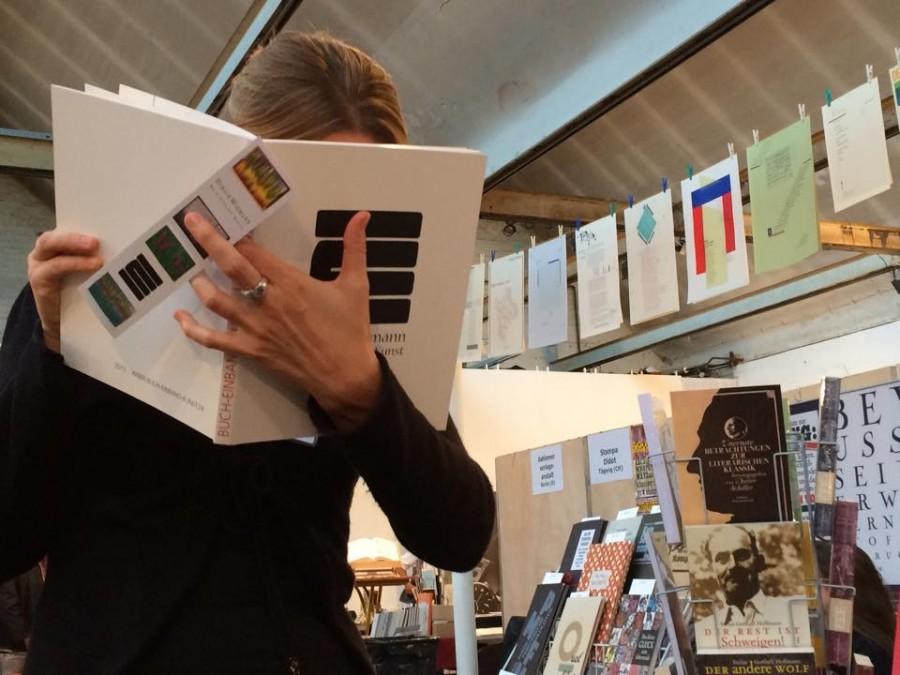 uha - Leserin mit Buchkunst von Buch-Einband-Kunst aus Freiburg i. Br., im Hintergrund der Stand von Edition Schwarzdruck aus Gransee (D)